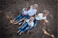 High angle view of four children sitting on sand in garden Stock Photo - Premium Royalty-Freenull, Code: 698-06374680
