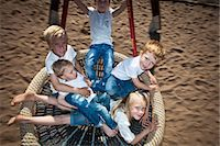 High angle view of happy children swinging in garden Stock Photo - Premium Royalty-Freenull, Code: 698-06374681