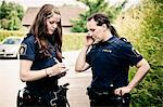 Female police officer using cell phone while colleague writing notes Stock Photo - Premium Royalty-Free, Artist: Robert Harding Images, Code: 698-06374903