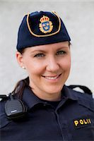 female police officer happy - Portrait of a happy young female police officer Stock Photo - Premium Royalty-Freenull, Code: 698-06374923
