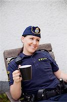 female police officer happy - Relaxed female police officer holding coffee cup Stock Photo - Premium Royalty-Freenull, Code: 698-06374927