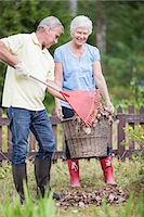 Portrait of a senior woman with man raking leaves in garden Stock Photo - Premium Royalty-Freenull, Code: 698-06374948