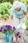 Senior woman watering flower pot with pitcher Stock Photo - Premium Royalty-Free, Artist: Atli Mar Hafsteinsson, Code: 698-06374956