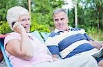 Senior man looking at woman on call while relaxing on lounge chairs Stock Photo - Premium Royalty-Free, Artist: Sheltered Images, Code: 698-06374962