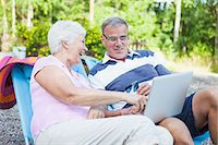 Happy senior couple shopping online together while relaxing on lounge chairs Stock Photo - Premium Royalty-Freenull, Code: 698-06374963