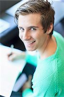 Portrait of a happy young man writing notes in classroom Stock Photo - Premium Royalty-Freenull, Code: 698-06374974