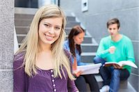 Portrait of a young female student with friends studying on steps in the background Stock Photo - Premium Royalty-Freenull, Code: 698-06374989