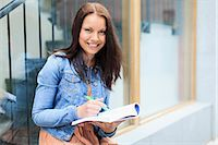 Portrait of a happy young female student with book and pen Stock Photo - Premium Royalty-Freenull, Code: 698-06375008