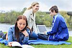 Three happy university students relaxing in campus lawn Stock Photo - Premium Royalty-Free, Artist: Blend Images, Code: 698-06375016