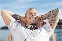 Happy man with tattooed hands relaxing on deck chair at beach Stock Photo - Premium Royalty-Freenull, Code: 698-06375052