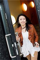 Portrait of a mid adult woman exiting through glass door Stock Photo - Premium Royalty-Freenull, Code: 698-06375139