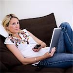 Mid adult woman with digital tablet changing channels with remote control on sofa Stock Photo - Premium Royalty-Free, Artist: Blend Images, Code: 698-06375166