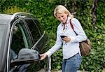 Mid adult woman looking at mobile phone and opening car door Stock Photo - Premium Royalty-Free, Artist: Blend Images, Code: 698-06375188