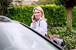 Mid adult woman using mobile phone by car Stock Photo - Premium Royalty-Freenull, Code: 698-06375190