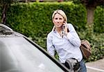 Mid adult woman using mobile phone by car Stock Photo - Premium Royalty-Free, Artist: Blend Images, Code: 698-06375191