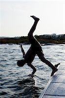 Silhouette of a little boy diving into water Stock Photo - Premium Royalty-Freenull, Code: 698-06375196