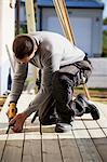 Manual worker drilling nail on floorboard Stock Photo - Premium Royalty-Free, Artist: Blend Images, Code: 698-06375229