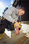 Manual worker drilling nail on floorboard Stock Photo - Premium Royalty-Freenull, Code: 698-06375232