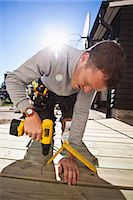 drilling - Manual worker drilling nail on floorboard against sunbeam Stock Photo - Premium Royalty-Freenull, Code: 698-06375233