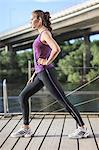 Side view of young woman stretching on footbridge