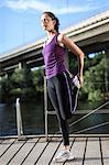 Side view of young woman stretching leg on footbridge