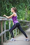 Side view of young woman stretching on fence Stock Photo - Premium Royalty-Free, Artist: Westend61, Code: 698-06375334