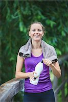 Portrait of smiling young woman holding water bottle Stock Photo - Premium Royalty-Freenull, Code: 698-06375336