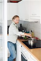 stove - Mid adult woman cooking in kitchen Stock Photo - Premium Royalty-Freenull, Code: 698-06375352