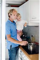stove - Man preparing food while holding daughter in kitchen Stock Photo - Premium Royalty-Freenull, Code: 698-06375354