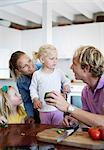 Couple with daughters in domestic kitchen Stock Photo - Premium Royalty-Free, Artist: Kablonk! RM, Code: 698-06375358