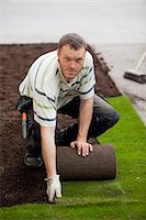 Portrait of a mid adult man rolling new grass turf in lawn Stock Photo - Premium Royalty-Freenull, Code: 698-06375476