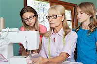 Granddaughters looking at grandmother sewing cloth Stock Photo - Premium Royalty-Freenull, Code: 693-06378762