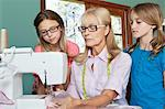 Granddaughters looking at grandmother sewing cloth Stock Photo - Premium Royalty-Free, Artist: Jason Friend, Code: 693-06378762