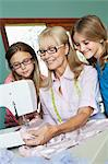 Girls looking grandmother sewing cloth Stock Photo - Premium Royalty-Free, Artist: Science Faction, Code: 693-06378763