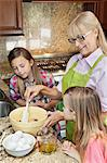 Senior woman with granddaughters mixing batter in kitchen Stock Photo - Premium Roya