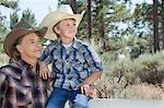 Mature father and son wearing cowboy hats looking away in park Stock Photo - Premium Royalty-Free, Artist: Kablonk! RM, Code: 693-06378789