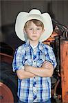 Portrait of a little boy wearing cowboy hat while standing with arms crossed against machine Stock Photo - Premium Royalty-Free, Artist: Blend Images, Code: 693-06378792