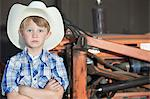 Portrait of a boy wearing cowboy hat while standing with arms crossed against machine Stock Photo - Premium Royalty-Free, Artist: Kablonk! RM, Code: 693-06378793