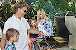 Family of four barbecuing Stock Photo - Premium Royalty-Free, Artist: Cultura RM, Code: 693-06378801