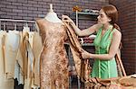 Young female fashion designer matching cloth with fabric draped on tailor's dummy Stock Photo - Premium Royalty-Free, Artist: GreatStock, Code: 693-06379023