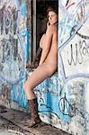 Naked young woman wearing boots as she sits on window sill Stock Photo - Premium Royalty-Free, Artist: Norbert Schäfer, Code: 693-06379186