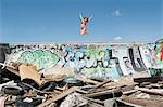 Young woman in bikini jumping over graffiti wall with garbage in foreground Stock Photo - Premium Royalty-Free, Artist: CulturaRM, Code: 693-06379188