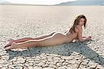 Naked young woman lying on cracked arid landscape Stock Photo - Premium Royalty-Free, Artist: CulturaRM, Code: 693-06379201