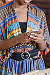 Midsection of woman in traditional African print attire using cell phone Stock Photo - Premium Royalty-Free, Artist: Bettina Salomon, Code: 693-06379227