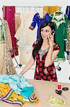 Pretty Indian female dressmaker answering phone call while standing at table Stock Photo - Premium Royalty-Free, Artist: Blend Images, Code: 693-06379290