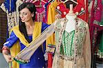 Indian female dressmaker measuring traditional outfit at design studio Stock Photo - Premium Royalty-Free, Artist: Blend Images, Code: 693-06379303
