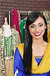 Portrait of a pretty Indian female dressmaker smiling Stock Photo - Premium Royalty-Free, Artist: Blend Images, Code: 693-06379312