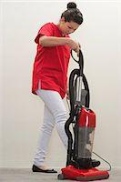 Full length of female housekeeper using vacuum cleaner Stock Photo - Premium Royalty-Freenull, Code: 693-06379358