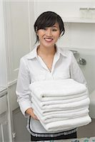Portrait of young female housekeeper holding clean white folded towels Stock Photo - Premium Royalty-Freenull, Code: 693-06379368