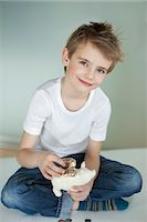 Portrait of young boy putting coin in piggy bank Stock Photo - Premium Royalty-Freenull, Code: 693-06379422